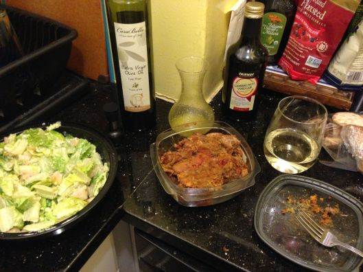 Leftover restaurant Caesar's salad doctored with my lamb stew and a glass of vino.